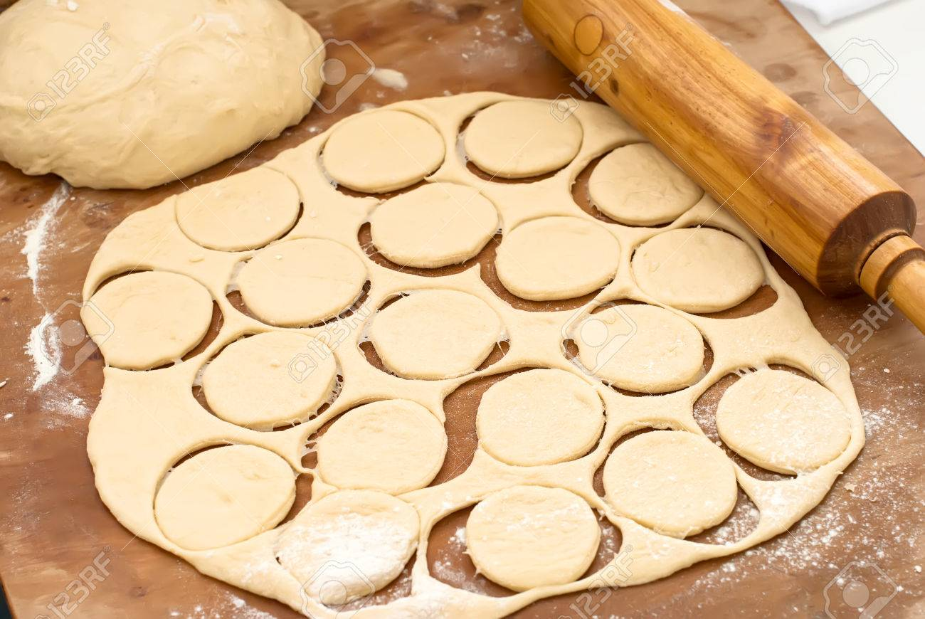 Ball Of Raw Dough, Rolling Pin And Cut Out Circles From Raw Cookie