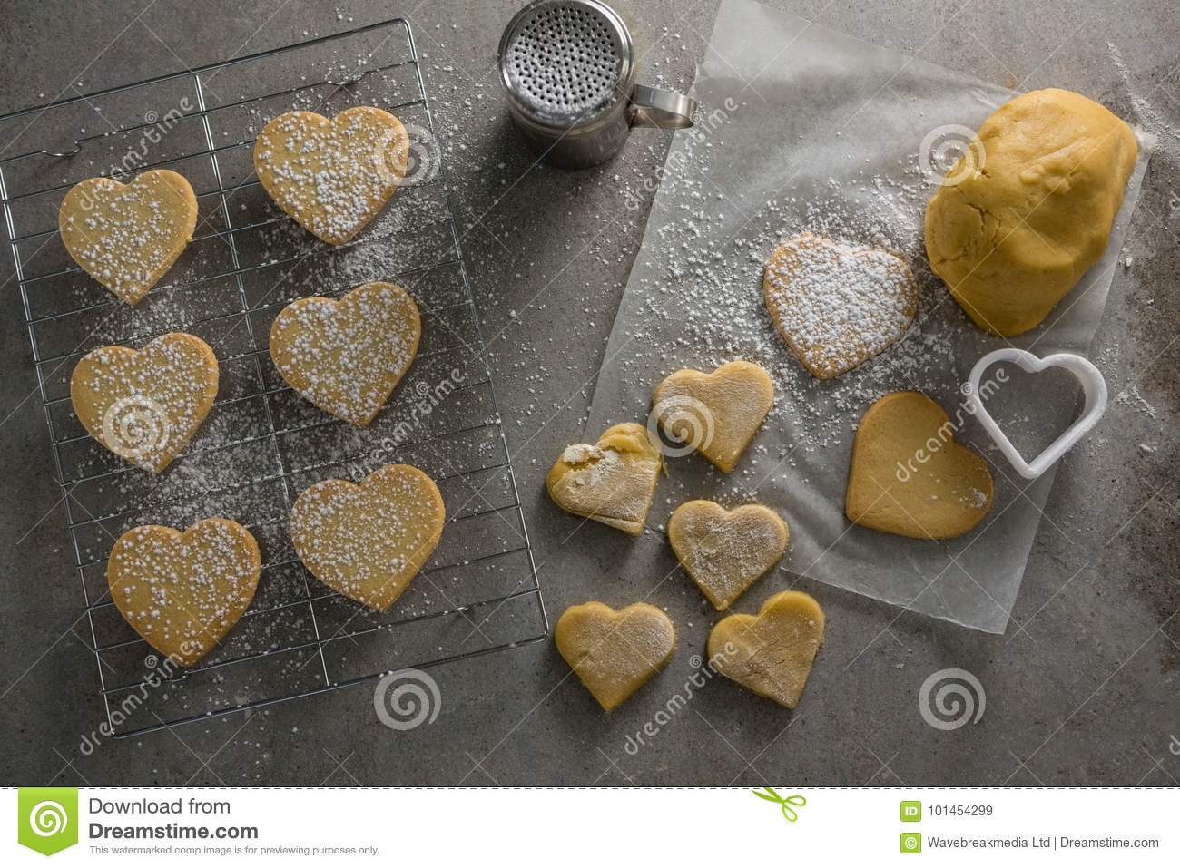 Raw Heart Shape Cookies On Baking Tray With Flour Shaker Strainer