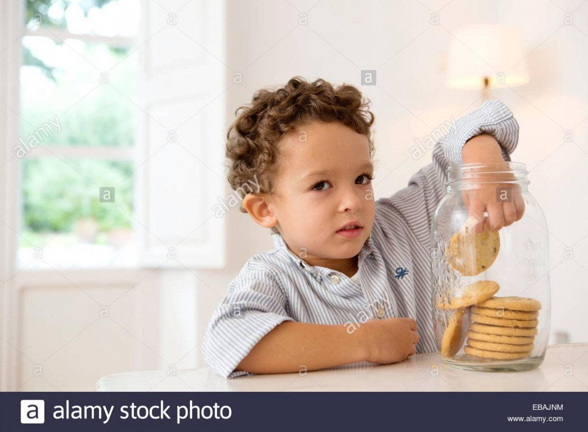 Four Year Old Boy With His Hand In The Cookie Jar Stock Photo