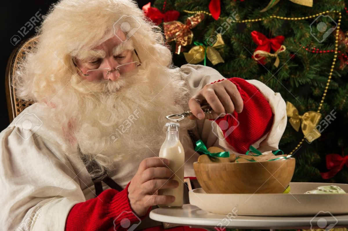 Santa Claus Eating Cookies With Milk Sitting Near Christmas Tree