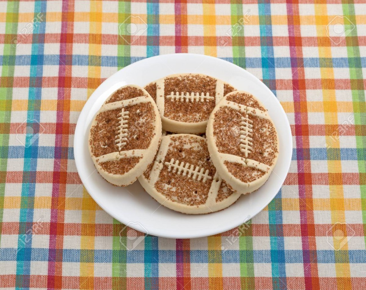 A Plate Full Of Football Shaped Sugar Cookies With Sprinkles