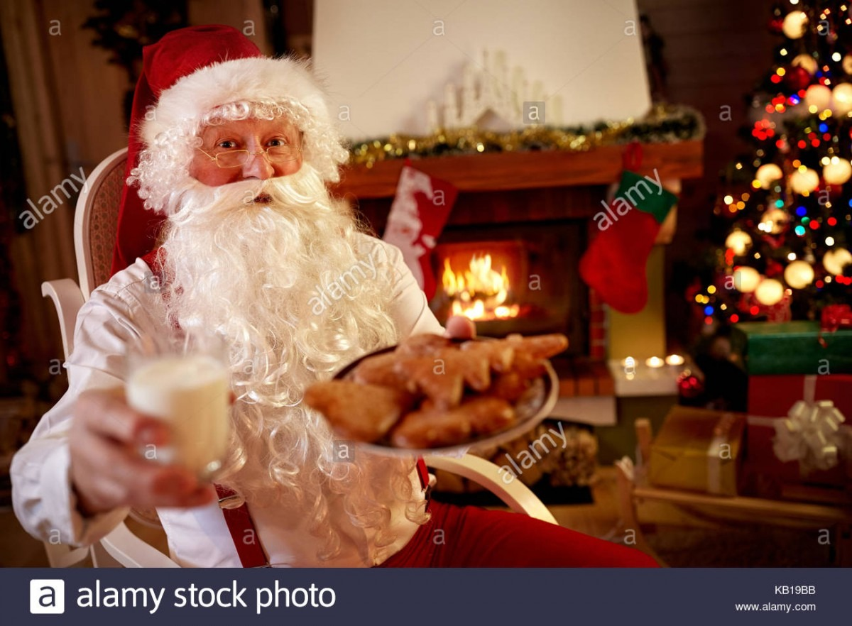 Santa Claus At Home Eating Cookies And Drinking Milk Stock Photo