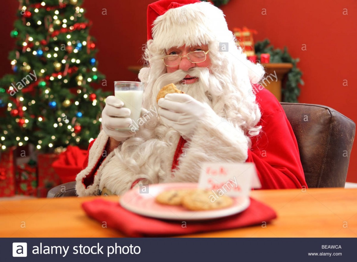 Santa Claus Eating Cookies With Glass Of Milk Stock Photo