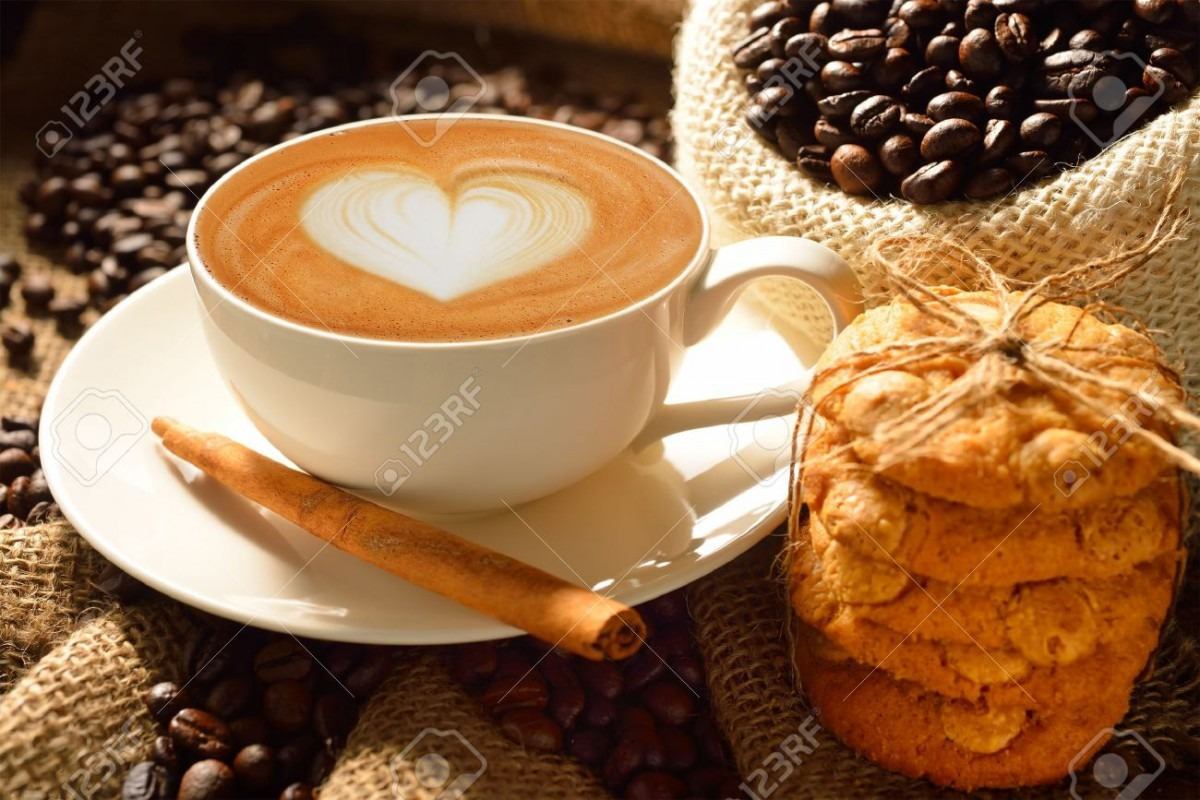 A Cup Of Cafe Latte With Coffee Beans And Cookies Stock Photo